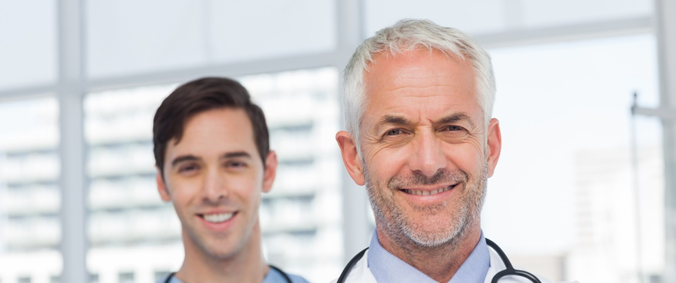 50s, Mature Adult, Man, Male, Caucasian, 20s, Young Adult, Indoors, Looking At Camera, Doctor, Practitioner, Profession, Professional, Specialist, Lab Coat, Stethoscope, Confident, Nurse, Scrubs, Blue, Standing, Clinic, Healthcare, Hospital, Medical, Staff, Attractive, Handsome, Grey Hair, Portrait, Team, Smiling, Happy, Cheerful, Friendly